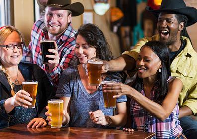 Firewaters Saloon people clinking beer glasses