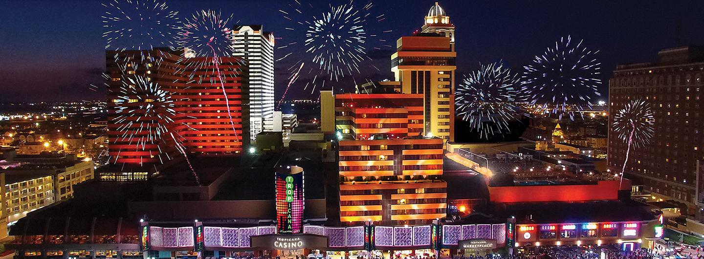Photo of Tropicana Atlantic City building front exterior at night lit up with city lights and fireworks