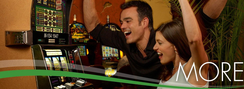 Two people enjoying slot machines