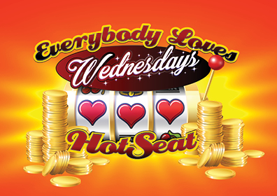 Bright orange background, in the center are the words, Everybody Loves Wednesdays under that is a slot machine image with 3 red hearts, under this are the words Hot Seat. To the left and the right are stacks of gold coins.
