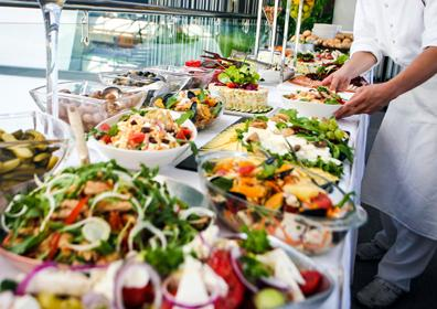 Beautiful Buffet table presentation with various types of food. Person dressed in white serving the food to the right of the photo.