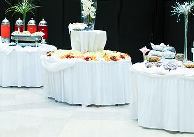 Three circular tables dressed with white table cloths.  Each table has a unique center piece and is displaying differnt types of food served at a party or wedding.  One of the tables is stacked and layered for additional culinary display.