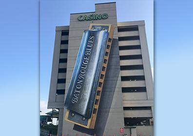 A large 10 story building made of gray concrete with spaces between each floor.  At the top is CASINO in green lights.  The front of this building has a large solid concrete panel the height of the entire building.  On this panel is a painting of a harmonica with the words Baton Rouge Blues down the side of the harmonica.