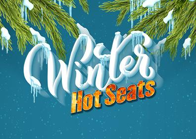 Teal background, green branches bowed with snow at the end at the top.  Centered in White cursive that looks like snow is the word Winter, beneath are the words Hot Seats in bright orange