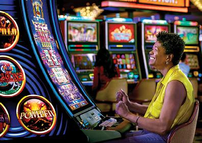 Casino slot machine image with African American w/yellow shirt in foreground and several other people in the background all playing slots.