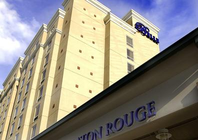 Belle of Baton Rouge brick hotel tower to the left with the word Belle on the top of the building in dark royal blue and the hotel entrance is to the right of the photo. Only the top of the building is shown and the words Belle of Baton Rouge are on the top of this building in a dark royal blue.