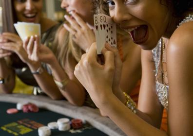 Group of three women seated playing a table game.  Closeup of one of the ladies, holding cards in her hand and smiling.  There are chips on the table.