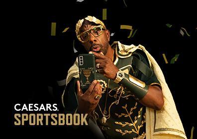 JB Smoove dressed in Caesars Football gear looking at his phone
