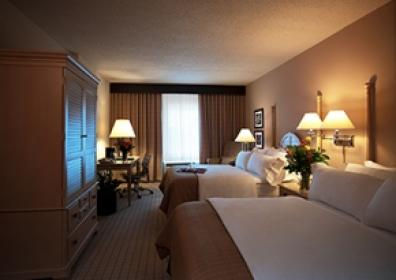 Standard Hotel Room with beds to the right of the room, window to the rear center, desk and entertainment center with tv to the left of the room.
