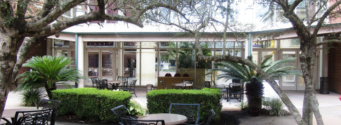A beautiful outdoor courtyard, large trees frame the left and the right.  Centered are 2 marble top wrought iron tables, each table has 4 wrought iron chairs placed around it.  To the rear are manicured green shrubs with additonal seating.  The back showcases a row of 14 glass doors entering into a large facility.