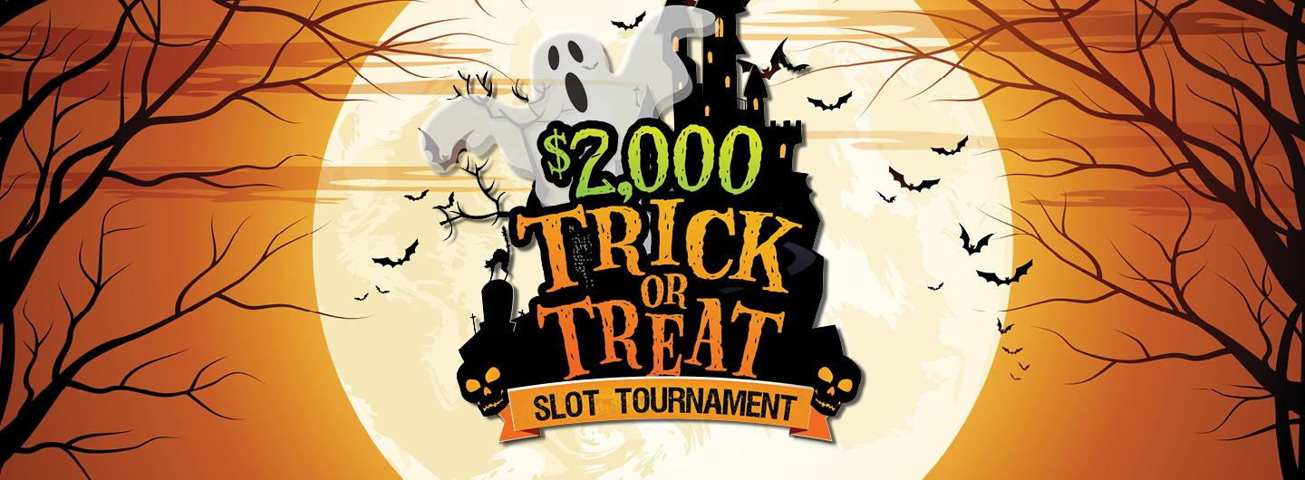 Spooky background effect images of tree shadows to the left and the right. In the Center a bright white moon with the image of a white ghost next to a black haunted house image with the words $2,000 (green) TRICK OR TREAT (orange), SLOT TOURNAMENT (black)