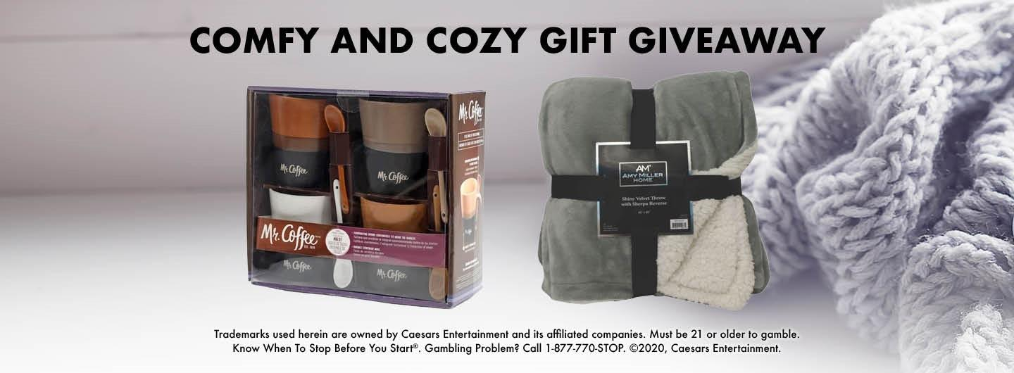 """Graphic Design: Gray background with soft blanket on right side  Centered are the words """"Comfy and Cozy Gift Giveaway"""" top, with middle picture of cups and blanket and bottom has disclaimer"""