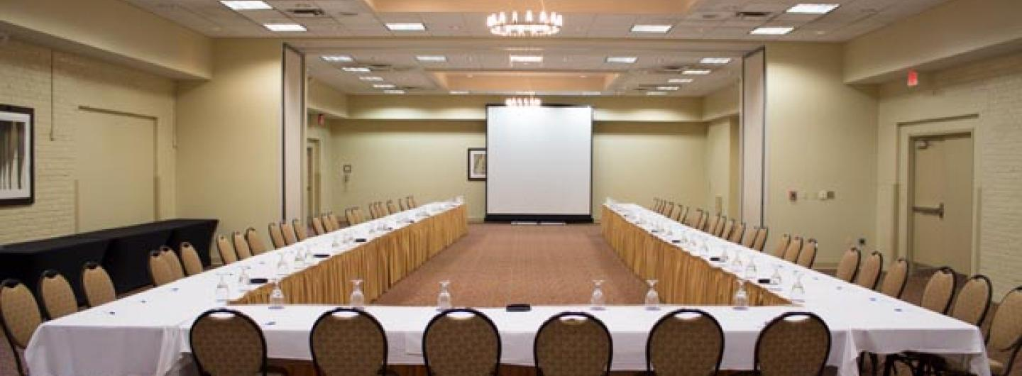 Large Meeting Room with a projector screen to the rear of the photo with table and chairs placed in a U shape around the screen.