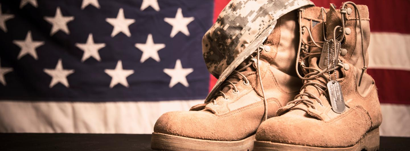 American flag background with worn and dusty military combat boots, military cap and metal dog tags hanging from top of the boots.