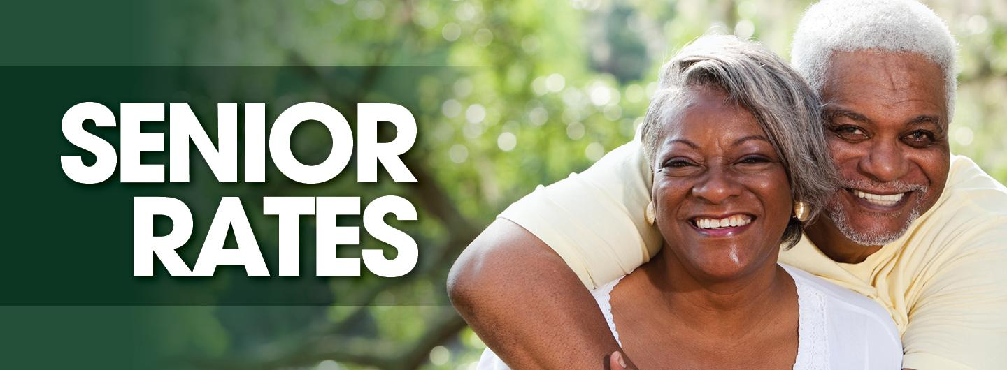 Green background with SENIOR RATES capitalized in white to the left.  To the right, attractive African American couple with gray hair both have big smiles.  The gentleman has his arm around the lady and both are wearing off white shirts.