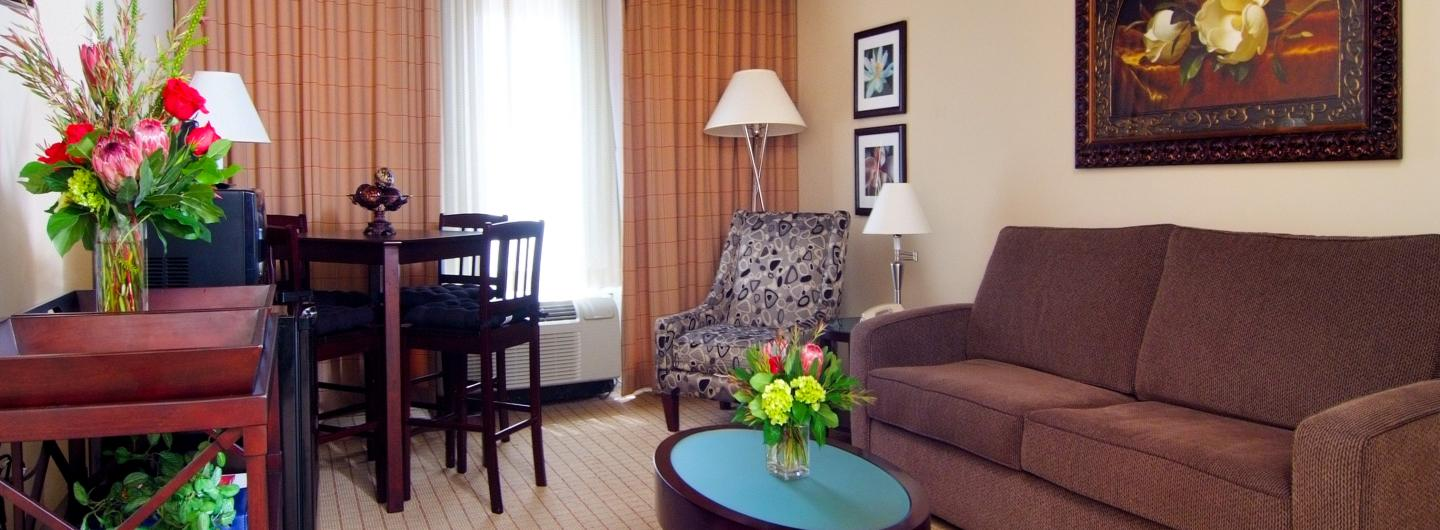 Junior Suite seating area is featured, center of the room is a coffee table with a fresh flower arrangement, to the right is a standard size brown sofa with framed artwork above it.  The rear center of the room is a window framed with beige plaid curtains, to the right is a floral armchair and floor lamp with framed artwork.  To the right of the window is a wooden table and 4 chairs, a small refrigerator and microwave