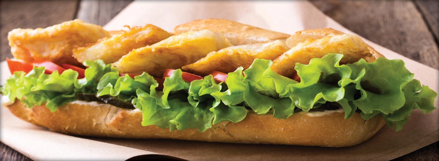 Picture of large po boy with lettuce and fried catfish on a plate