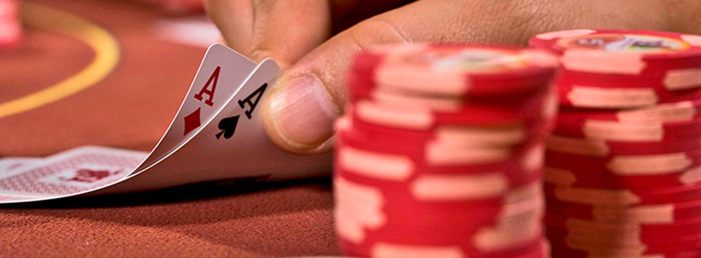 A person playing poker with two aces and a stack of chips