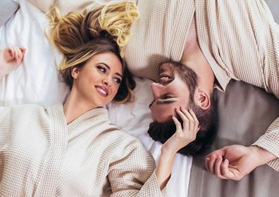 Man and women laying on a bed looking at each other