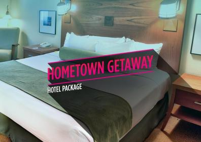 "Picture of a hotel room bed with the text, ""Hometown Getaway Hotel Package"""
