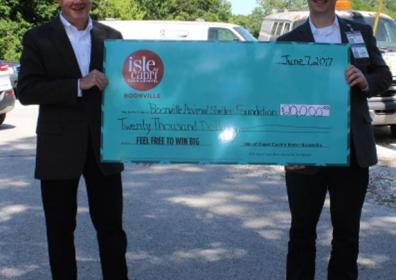 two men in suits holding a check