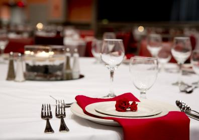 Banquet table decorated with cutlery, napkins and flowers