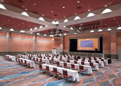 Banquet room with long tables and chairs set for meeting