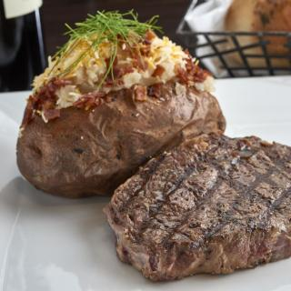 ribeye steak with loaded baked potato