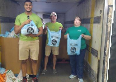 Rajaye, Roger, and Michelle loading the food truck for stamp out hunger.