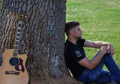 Photo of the lead singer, Eli Tellor leaning up against a tree
