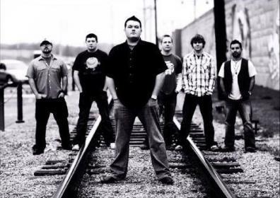 Photo of the band The Intention standing on a rail road track