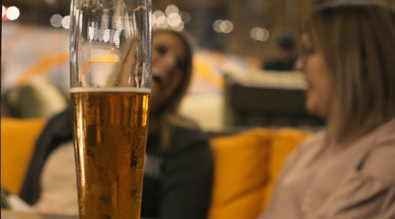 Beer glass with laughing guests in background