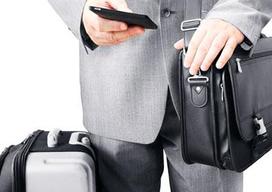 A business traveler with his luggage and cell phone