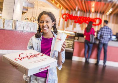 A girl holding a Piezzetta pizza box