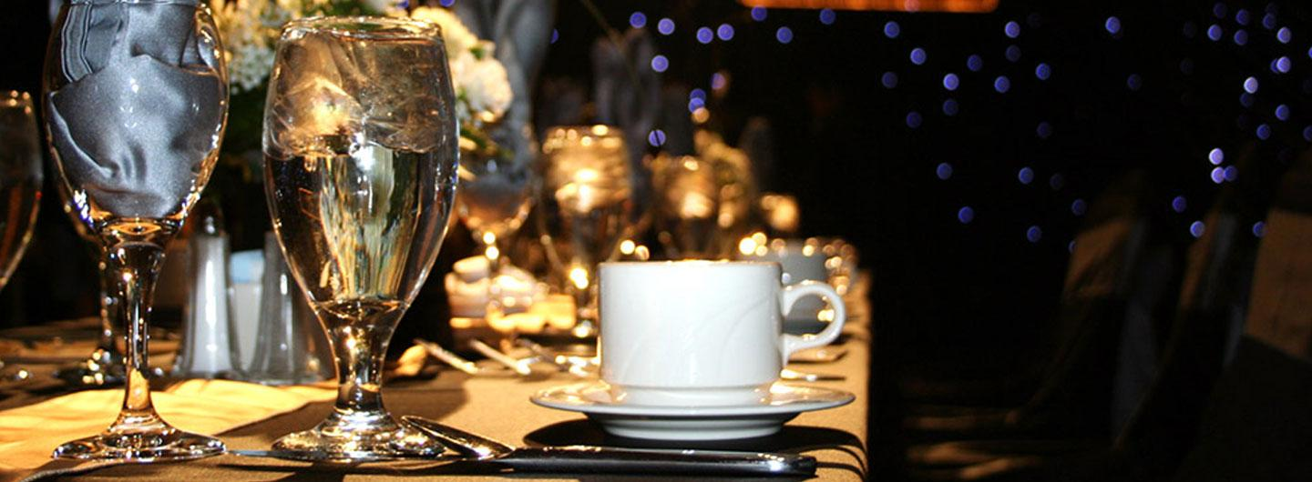 A table set up for an event with a coffee cup, glass of water, and wine glass