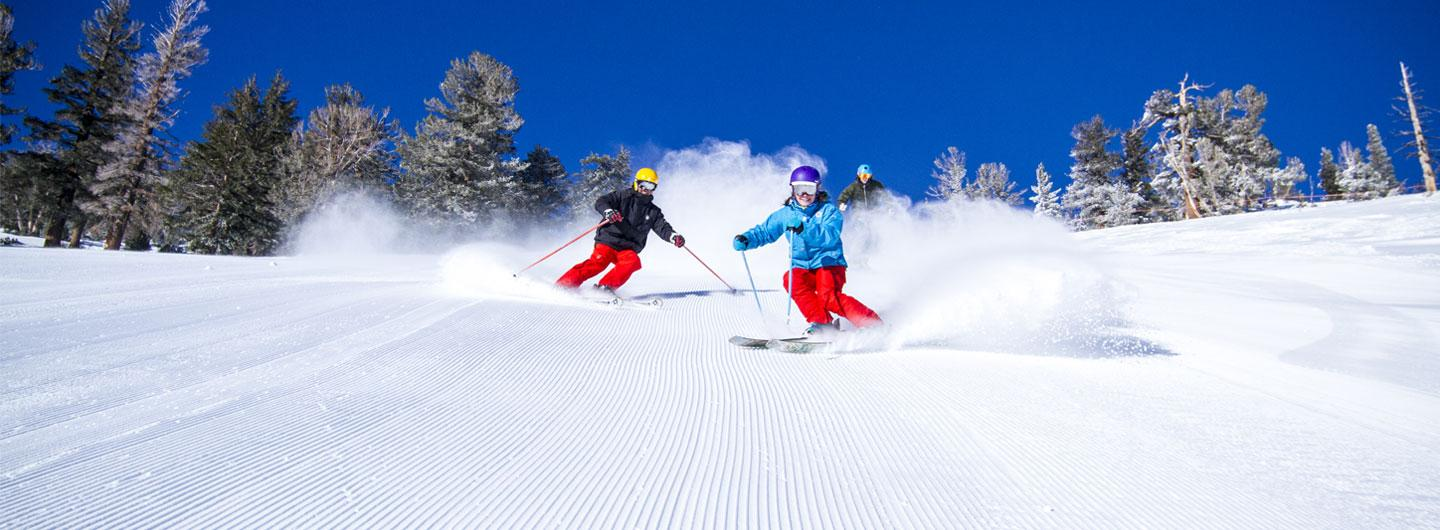 Skiers sking down snow covered mountain