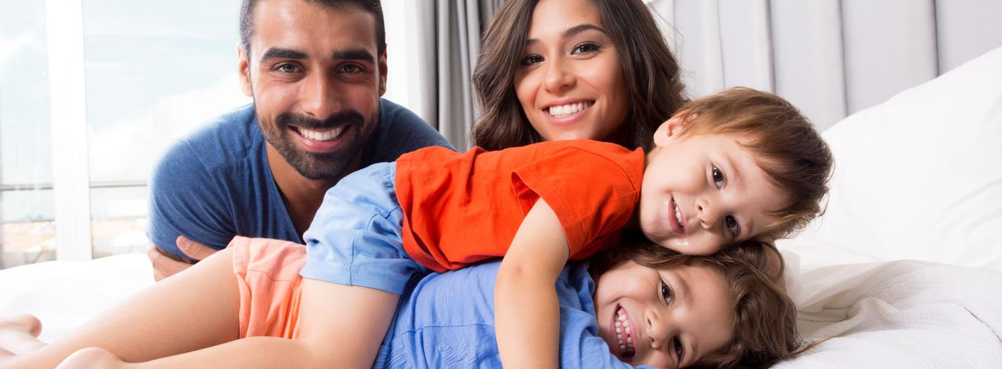 Happy family relaxing in bed