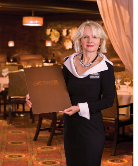 Steakhouse maitred holding menu.