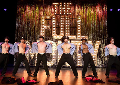 Men in police hats tearing of their shirts on a stage
