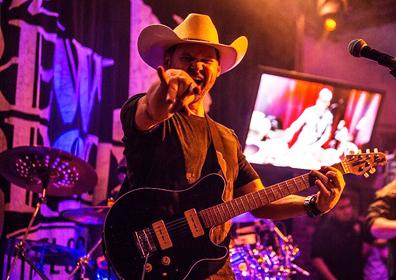 Guitarist rocking out on Brew Brothers stage with Cowboy Hat