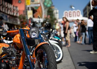 View of Orange Motorcycle with line of Bikes behind it and Crowd on Virginia Street