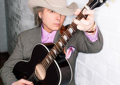 Dwight Yoakam wearing a cowboy hat playing guitar