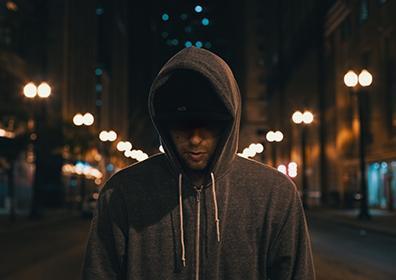 Artist Derek Vincent Smith staring towards the ground wearing hoodie on dark street
