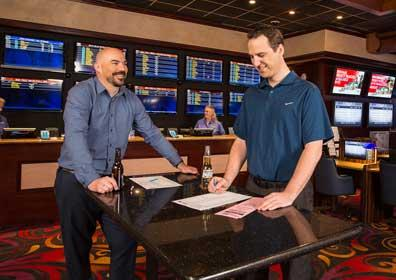 2 Men Drinking Beer and Betting on Teams in Sportsbook