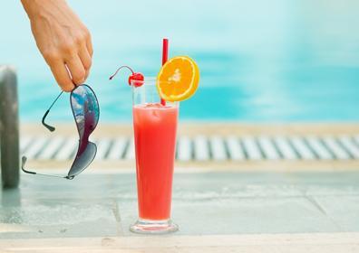 Sunglasses and Orange Tropical Drink by Eldorado Pool