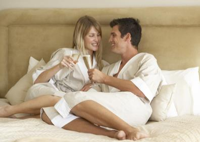 Couple in hotel bed drinking champagne