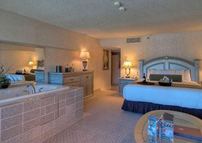 The suite is adorned with a California king bed, a jetted spa tub, a small living area, a cocktail table with two chairs.