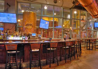 View of The Brew Brothers Bar with TVs and the large Brewing Equipment behind Glass Wall