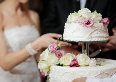A bride and groom in front of their wedding cake