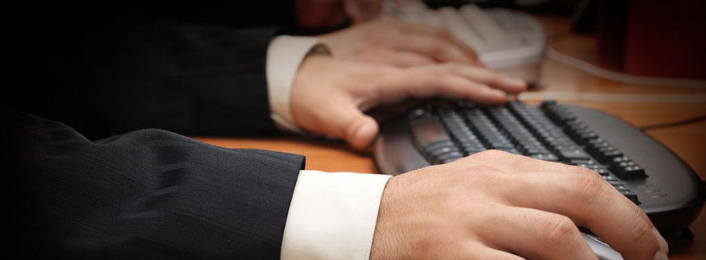 A man on a computer with just his hands and the keyboard showing for the business center